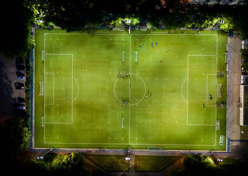 Aerial view of football pitch at night with amateur football players playing the game in the city