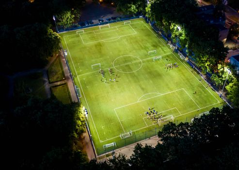 Football players running around the football field. Night workout. Preparation for the match. Aerial shot with a drone from a altitude