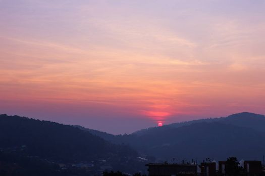 Sun setting over hills in a thai village near mountains in Chiang Mai, Thailand. The mountain scenery view