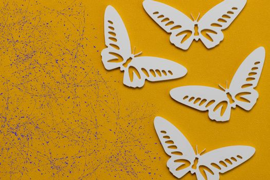 Minimal flatley composition, top view. White butterflies on a yellow background, a creative minimal concept, copy space.