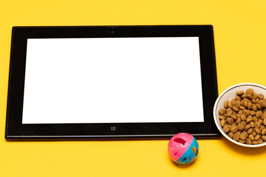 buy pet food and toys online via the app on your tablet, on a yellow background with a copy of the space. The concept of online shopping, electronic payment for services. Online purchases