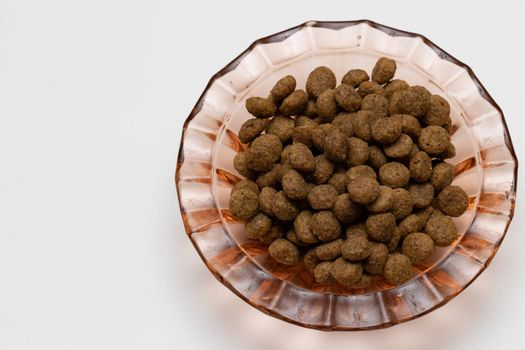 Balls of cat food in a beautiful bowl on a white background, isolate. The concept of pet food.