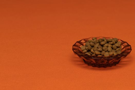 Balls of cat food in a beautiful bowl on an orange background, isolate. The concept of pet food.