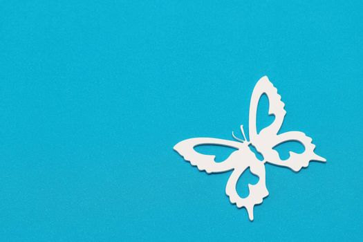 Minimal flatley composition, top view. White butterflies on a blue background, a creative minimal concept, copy space.