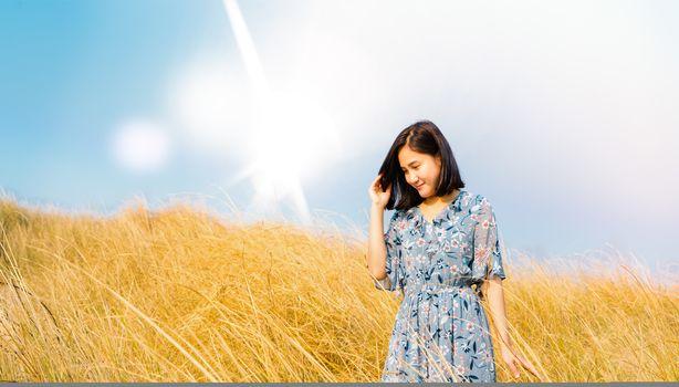 Asia Girl Outdoors enjoying nature. girl in blue dress walking on the Spring Field, Sun Light.