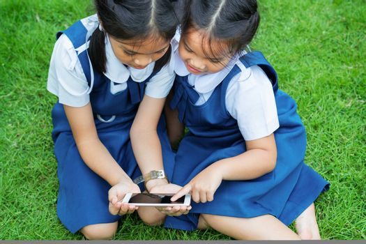 two little sister girls playing internet with mobile smartphone on grass