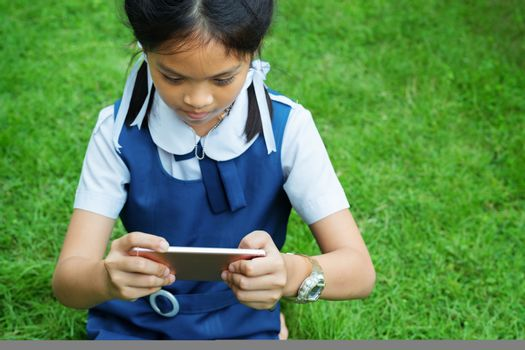 cute little girls playing internet with mobile smartphone on grass