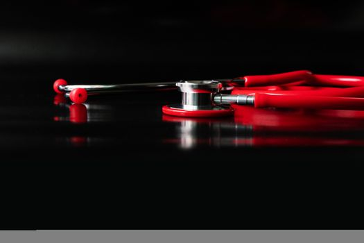 red stethoscope on black background. Healthcare and medicine con
