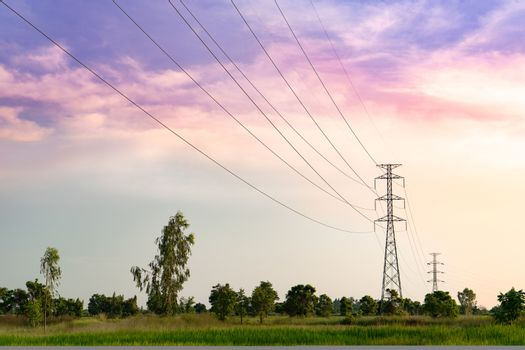 distant high voltage tower on the field sunset scene