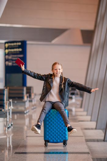 Little adorable kid in airport with passport waiting for boarding indoors