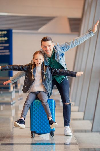 Young father and little daughter at international airport waiting for boarding