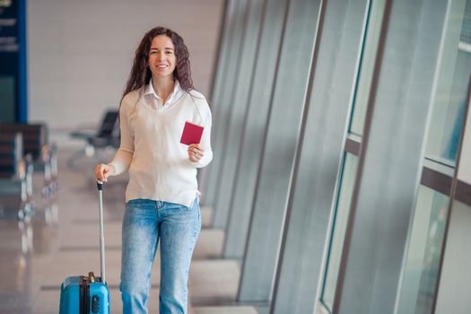 Young woman with luggage in international airport. Airline passenger in an airport lounge waiting for flight aircraft