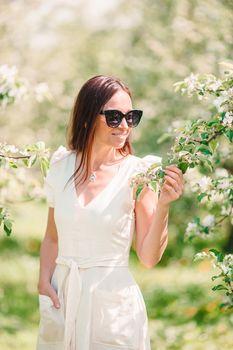 Beautiful woman enjoying smell in spring cherry garden