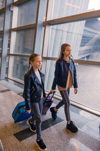 Little adorable kids in international airport with luggage
