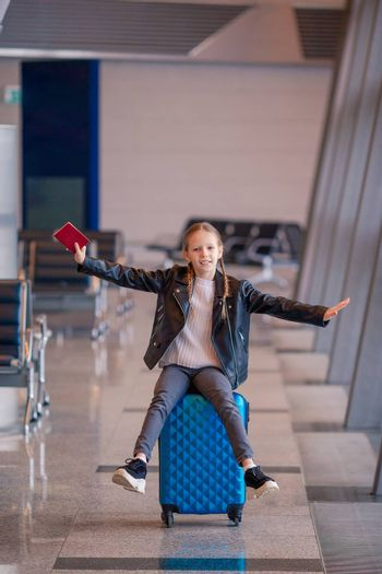 Adorable girl in airport with passport waiting for boarding in international airport