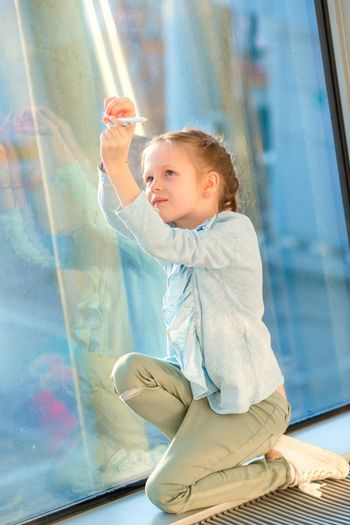 Little girl with long hair in airport near big window while wait for boarding