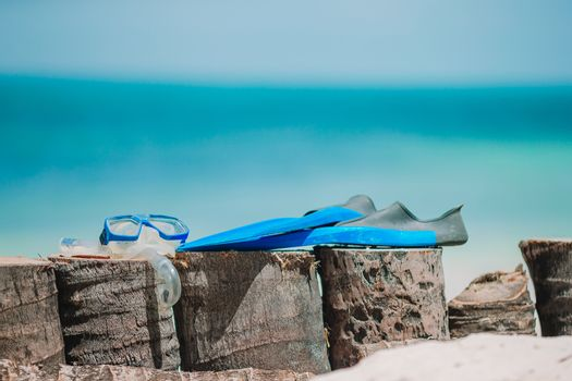 Snorkeling equipment mask, snorkel and fins on white beach