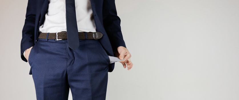 A man in a business suit turned his pockets inside out. Financial crisis. Bankruptcy in business. An entrepreneur without money.