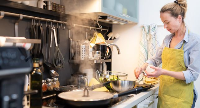 Stay at home housewife woman cooking in kitchen, salting dish in a saucepan, preparing food for family dinner. Blonde caucasian model in her 30is, real cooking not looking in camera.