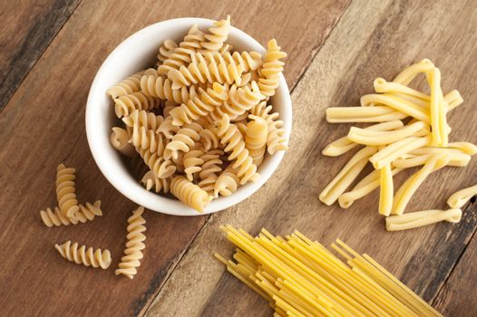 Assortment of dried Italian pasta on wood