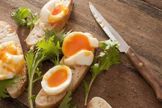 Tasty soft boiled eggs and salad greens