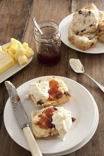 Fresh buttered rock cake with cream and fruit jam