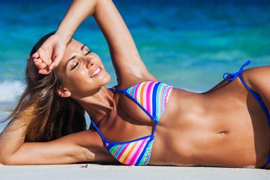 Beautiful tan girl in bikini lies on tropical sea beach
