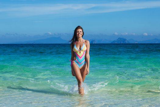 Happy tanned girl in bikini at seaside, blue sea water on background