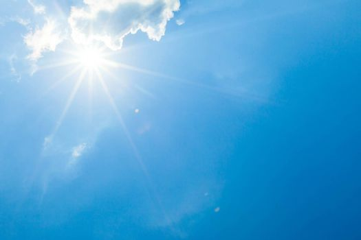 Blue sky with clouds and sun lens flare effect copy space for text