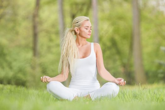 Yoga girl in lotus pose in the park, young woman in white clothes sitting on fresh green grass