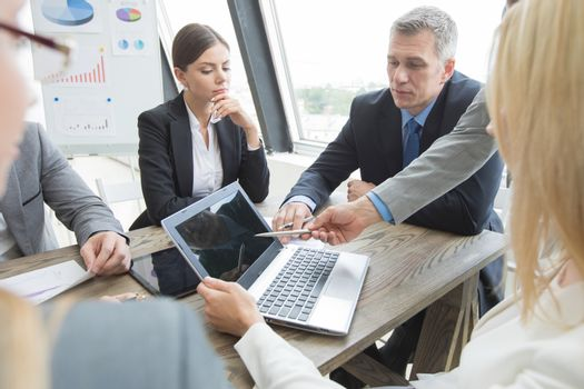 Team of business people at meeting in office discuss financial data using laptop