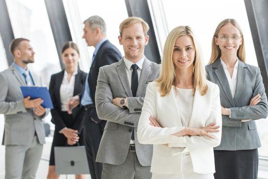 Portrait of businessteam standing in office, smiling, senior executive people in focus
