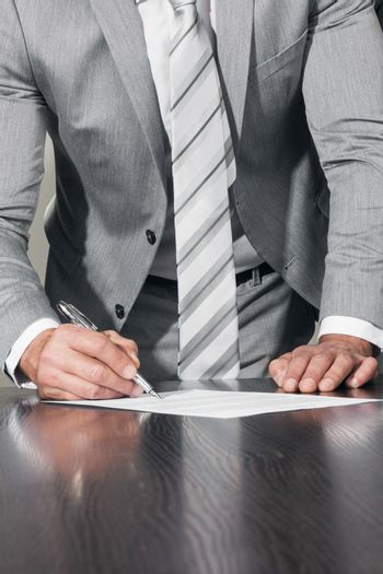 Work process and deal concept. Businessman with pen in hand reading official business contract before making a deal and signing document, close up view