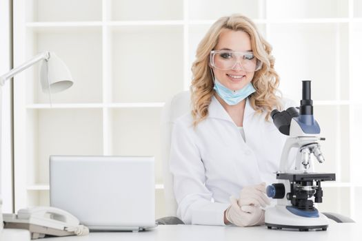 Portrait of a female researcher or medical doctor doing research using microscope in a laboratory