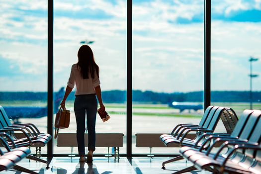 Young woman in international airport with her luggage background big window. Airline passenger in an airport lounge waiting for flight aircraft