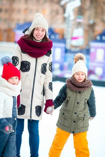 Family skating on ice-rink with mother