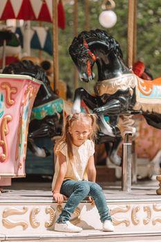 Adorable little girl near the carousel outdoors