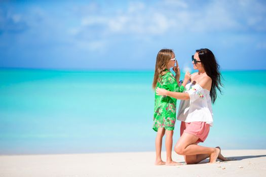 Little girl and young mother on the beach. Parent love.