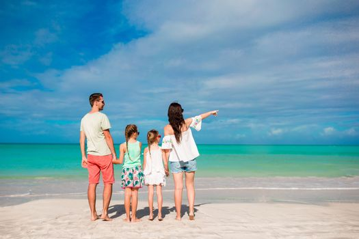 Happy beautiful family on the beach. Back view of parents and kids on Carribean