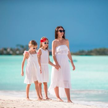 Beautiful mother and adorable little daughters at beach