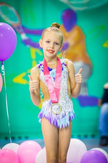 Little charming gymnast with medal after the rhythmic gymnastics competition
