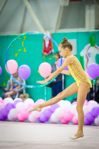 Little beautiful gymnast on carpet. Adorable gymnast participates in competitions in rhythmic gymnastics