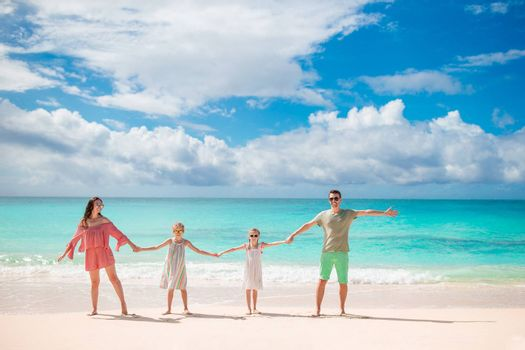 Happy beautiful family on white beach having fun together