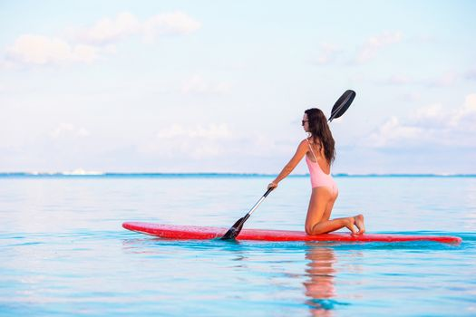 Active young woman on stand up paddle board
