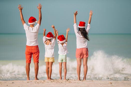 Happy family in Santa hats on a tropical beach celebrating Christmas vacation