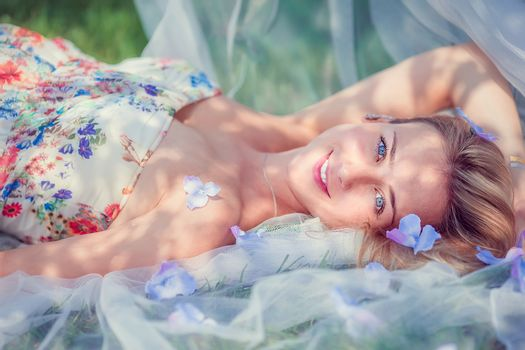 Lovely tender pregnant woman relaxes resting on the grass in the park on a warm day. Pregnancy concept