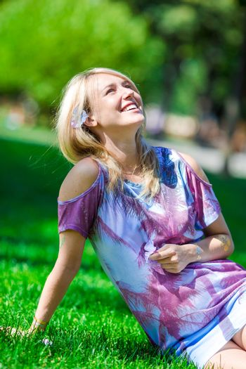 Pregnant woman in outdoor park warm weather. Pregnancy concept - pregnant woman over sunny summer background