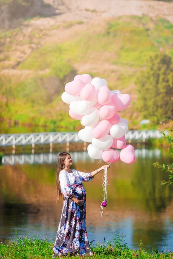 Pregnant woman with a bunch of balloons in outdoor park warm weather.