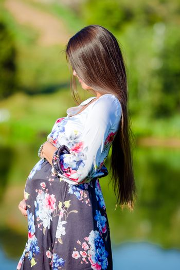 Pregnant woman holding on belly over sunny summer background in the park outdoors