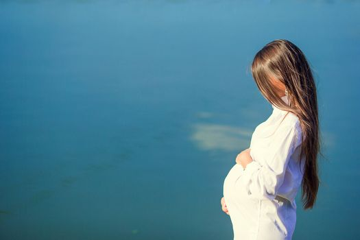 Beautiful pregnant woman outdoor near the lake. Pregnancy concept - pregnant woman in white shirt holding on belly over sunny summer background